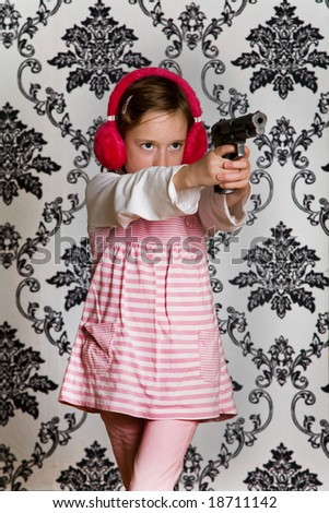 Young girl playing with a toy gun and wearing red ear defenders