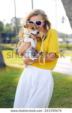 Young girl playing with her dog on the beach.Wear beautiful yellow shirt on white skirt enjoy her time.having fun.Glowing skin,summer store,woman playing with dog.Summer outdoor collection,sunglasses - stock photo