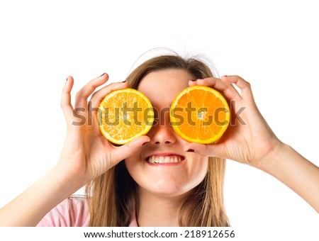 Young girl playing with oranges over white background