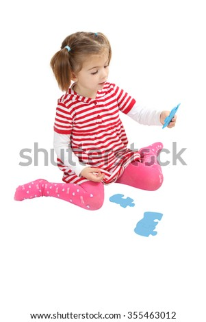 Young Girl Playing With Puzzle Pieces. white background - stock photo
