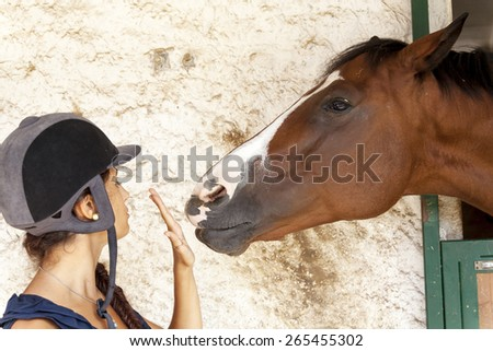 young girl plays with his horse - stock photo