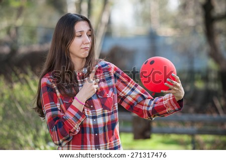 Young girl pointing and looking at the red balloon horizontal - stock photo