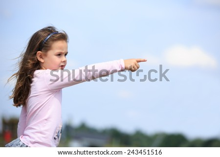 Young girl pointing her finger - stock photo