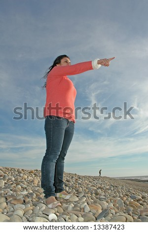 young girl pointing her finger to sky