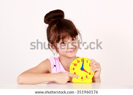 Young girl pointing to clock, learning to tell time. - stock photo