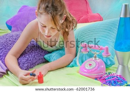 Young girl polishing nails in room - stock photo