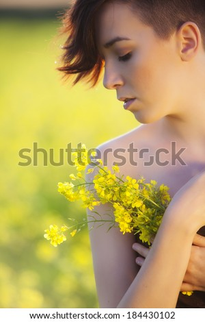 Young girl portrait holding yellow flowers - stock photo