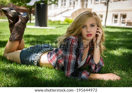 Young girl posing and laying wearing flannel shirt and boots - stock photo