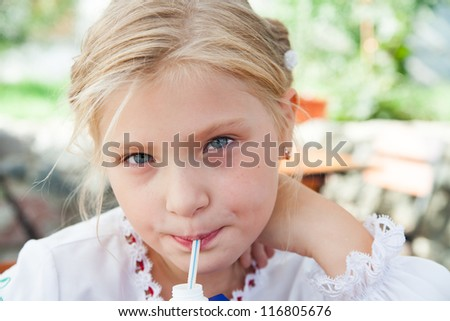 Young girl  posing in an outdoor cafe and sipping juice with a straw - stock photo