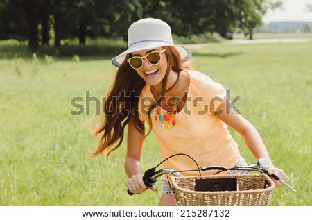 young girl posing in the park on bike - stock photo