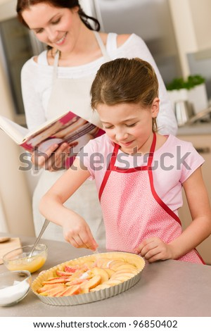 Young girl prepare home tart with mother adding sugar