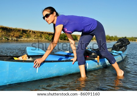 Young girl pulling a canoe - stock photo