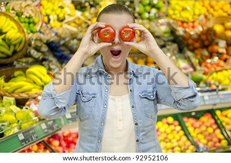 Young girl puts two tomatoes in front of her eyes and makes a funny face