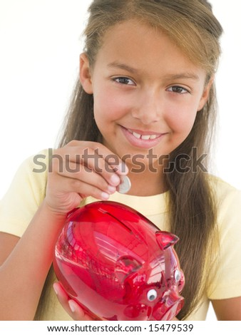 Young girl putting coin into piggy bank smiling - stock photo