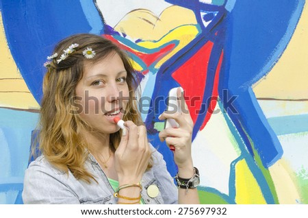 Young girl putting lipstick on using smart-phone as a mirror - stock photo