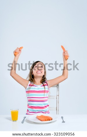 Young girl raises her arms and looks up holding carrots in her hands, happy healthy child eating concept  - stock photo