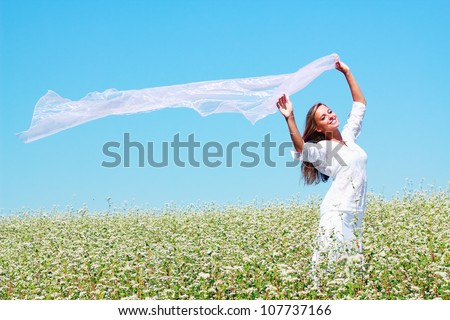 Young girl raising her hands with fabric on field with flowers - stock photo