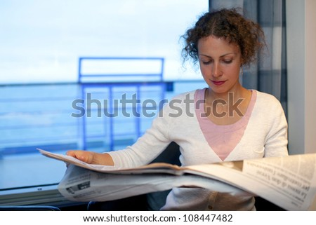 Young girl read newspaper in cabin of big passenger ship with view on sea - stock photo