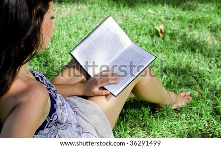 young girl reading a book at the park - stock photo