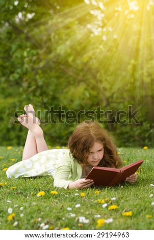 Young girl reading a book outdoors in summertime - stock photo
