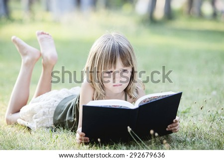 Young girl reading a book while lying in the grass - stock photo