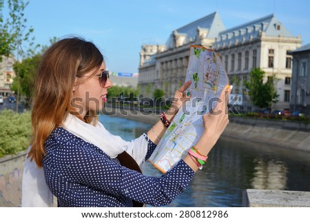 Young girl reading a map close to a river in Bucharest
