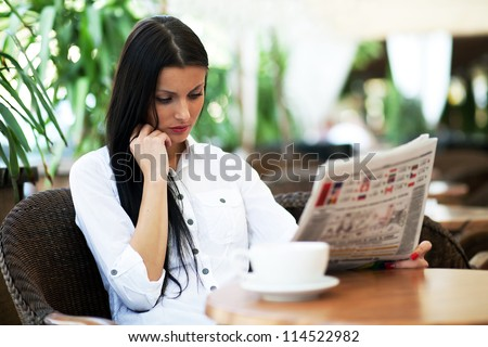 Young girl reading a newspaper during the job break - stock photo