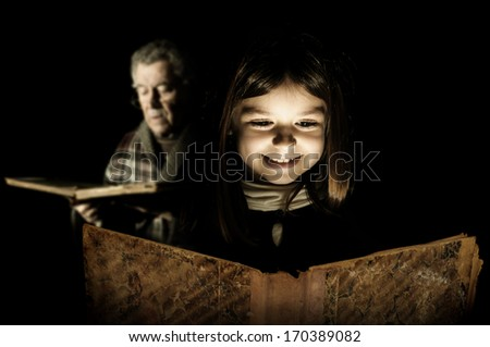 Young girl reading a very old book with grandfather in the background - stock photo