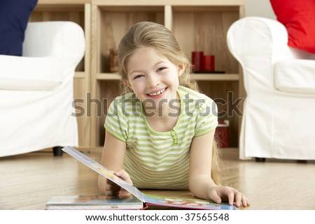 Young Girl Reading Book at Home - stock photo
