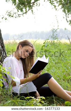 Young girl reading book in park in summer day