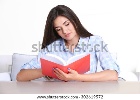 Young girl reading book in room