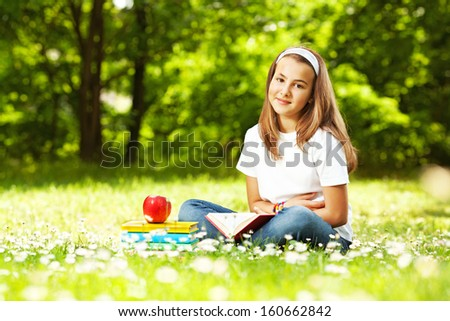 Young Girl reading book in the park, on a break - stock photo