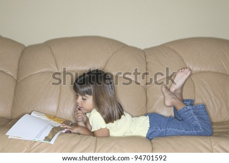 Young girl reading book on sofa - stock photo
