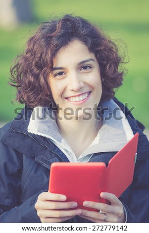 young girl reading E-book at park