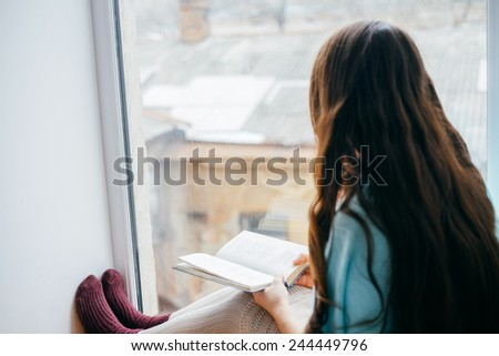 Young girl reading with book by the window - stock photo