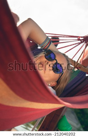 Young Girl Relaxing In Hammock Near River - stock photo