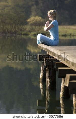 young girl relaxing on pier in early morning - stock photo
