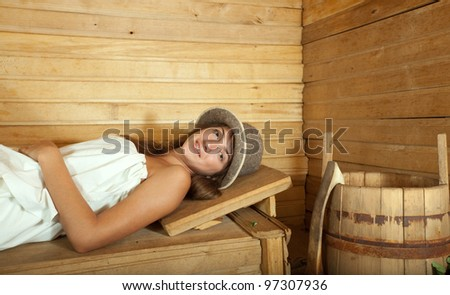 Young girl relaxing on wooden bench in sauna
