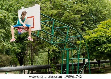 Young girl replacing a basketball net sitting balanced on top of the metal hoop carefully threading the net onto the ring, against greenery with copyspace - stock photo