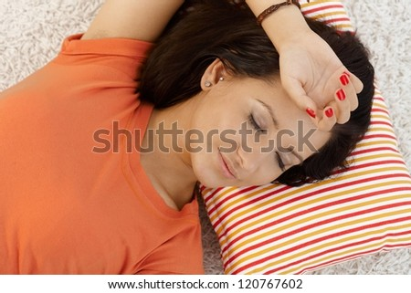 Young girl resting at home on pillow eyes closed. - stock photo