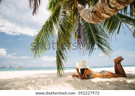 Young girl resting on a paradise beach - stock photo