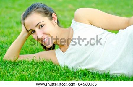 Young girl resting on grass smiling beautifully - stock photo