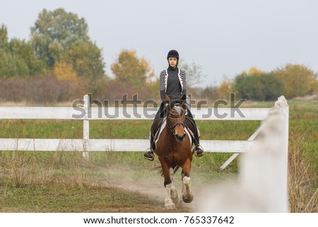 young girl ride her horse in the yard