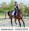 young girl riding a horse - stock photo