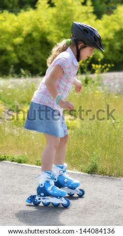 Young girl riding on roller skates. - stock photo