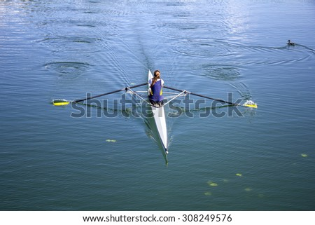 Young girl rower training rowing on the lake, to her wild duck  - stock photo