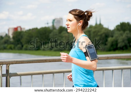 young girl running in the city, over the river by the bridge - stock photo
