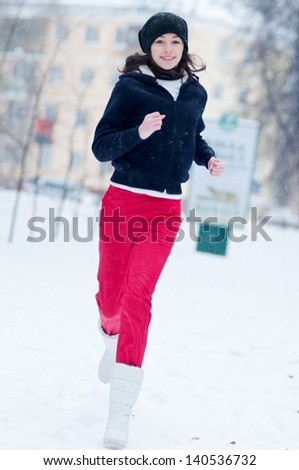 Young girl running on a cold winter day outdoor