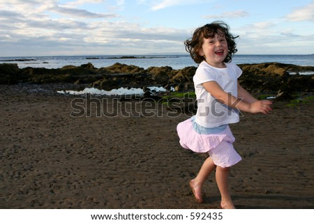 Young girl running on the beach - stock photo