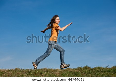 Young girl running outdoor against blue sky